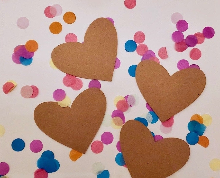 Photo of 4 brown hearts on top of confetti