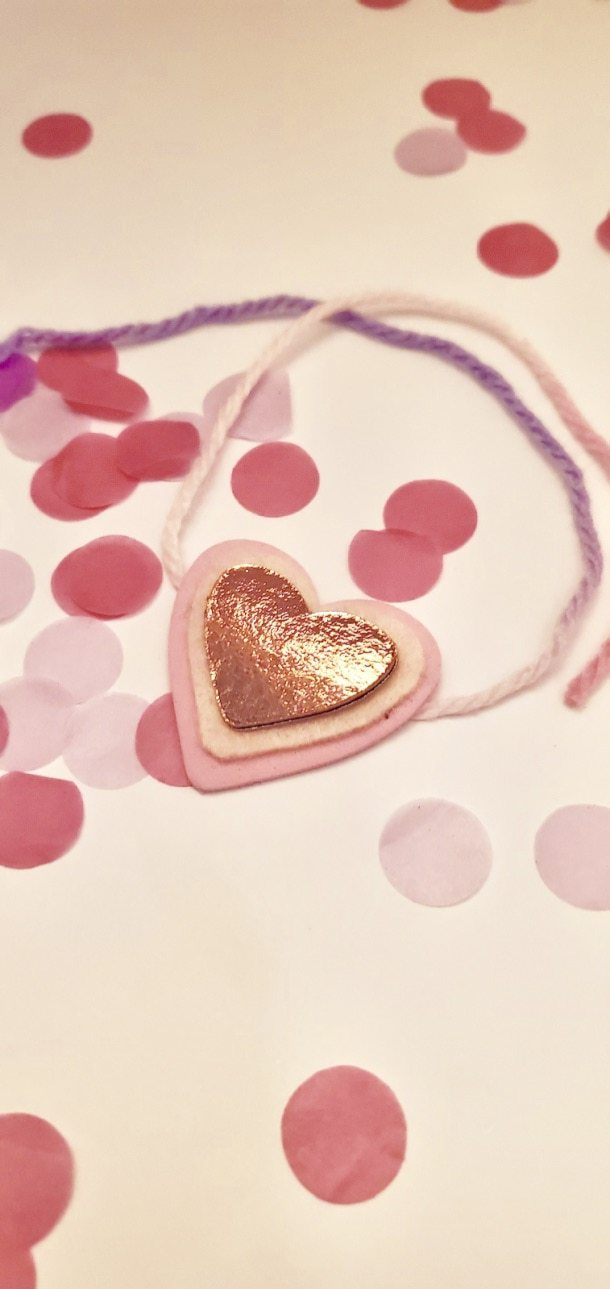 Picture of a bracelet with three pink hearts on top of pink confetti