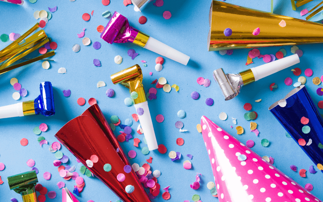 Picture of party hats, noise makers, and confetti on a blue table