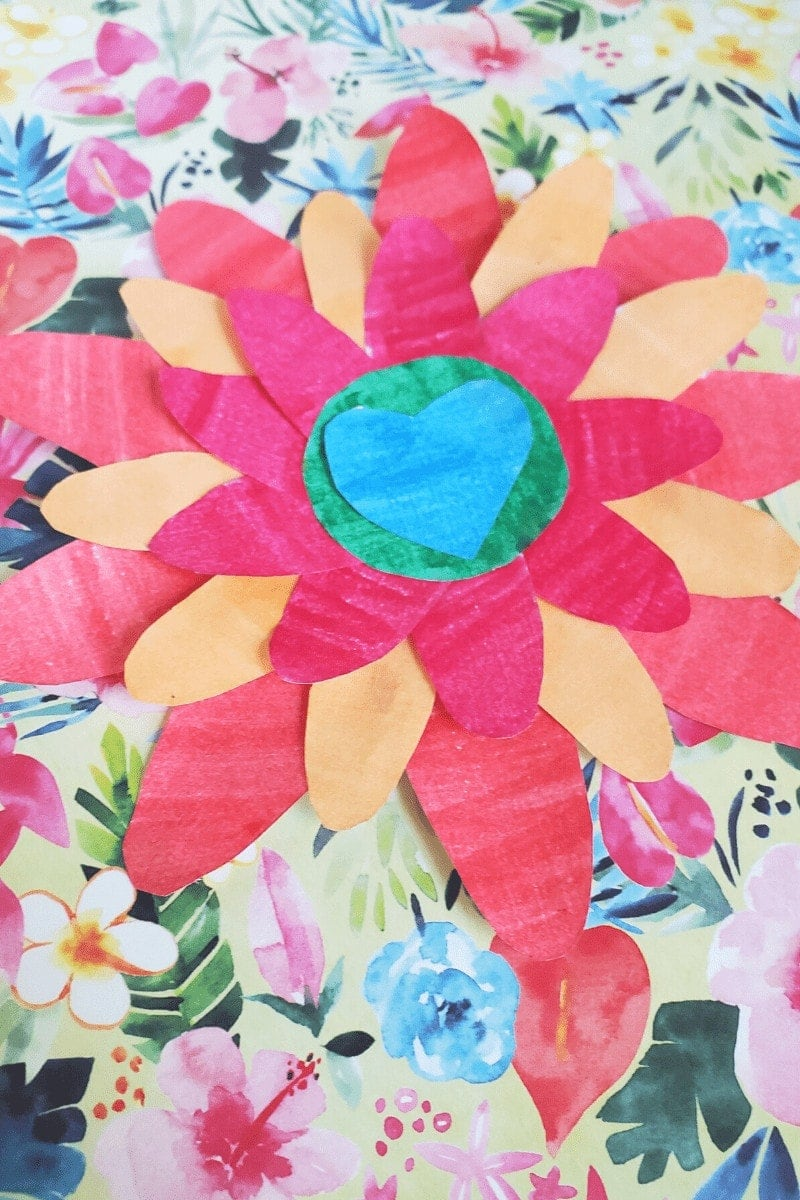 Photo of a layered flower made out of paper, sitting on a floral background