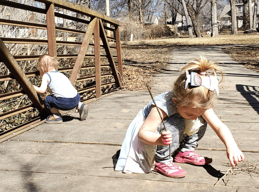 girl playing with sticks on a bridge, boy looking out the side of a bridge