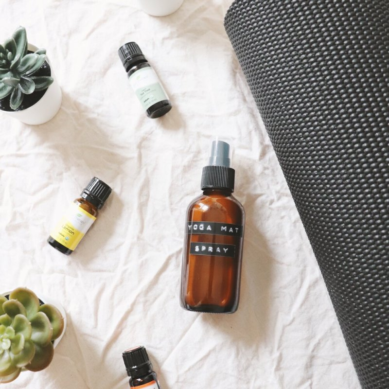 A brown spritz bottle of DIY yoga mat cleaning spray lays on a white towel next to various bottles of essential oils, a dark grey yoga mat, and a variety of faux succulents