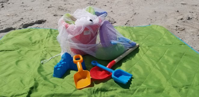 Easy Beach Hack for Sand toys - use a mesh bag to hold your toys so you can keep the sand off your blanket and car. Just shake the mesh bag and let all the sand fall out.