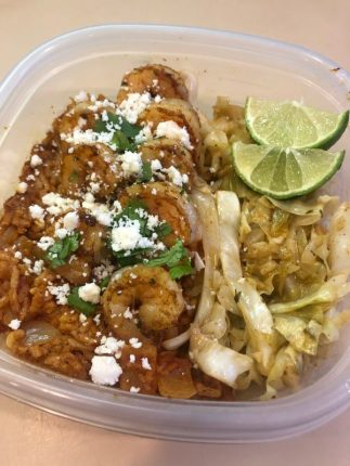 Spicy shrimp and cabbage over Mexican rice, garnished with cojita cheese, cilantro, and lime wedges
