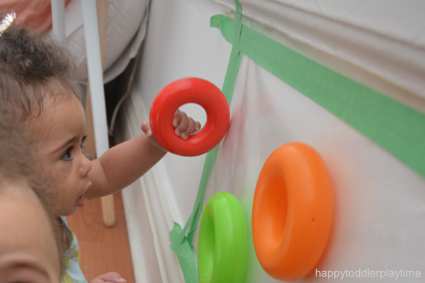 babies sitting and playing with rings and contact paper