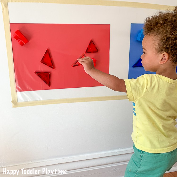 toddler Colour sorting red and  blue on a sticky wall
