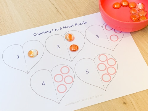 Toddler counting and covering the circles on the printable.