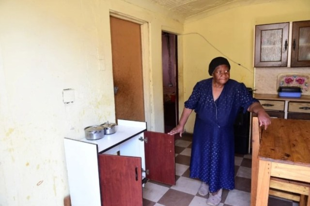 Gogo standing in her kitchen where two plate gas stove, microwave and some chairs disappeared. Photo by Morapedi Mashashe .