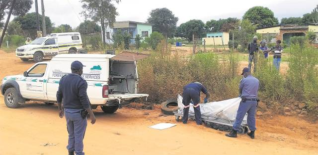 Police and a forensic pathologists removing the burnt body of the suspect who was set alight by angry residents after accusing him of rape. Photo by Tlangelani khosa.