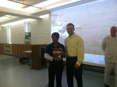Ameena receiving an ArcGIS tutorial book from Dave LaShell, ESRI