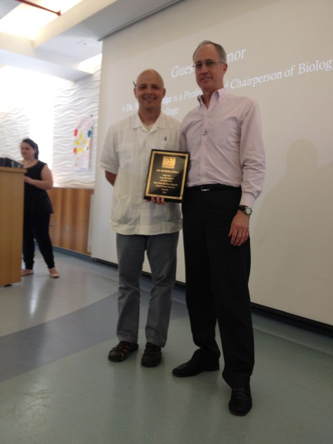 Dr. Michael Judge being presented a plaque by Mauricio Gonzalez in recognition of his longstanding collaboration with the Marine Biology Research Program