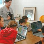 "Children decipher codes using real-life examples while playing ""Drag and Drop Coding"" during the Hour of Code and Winter Break Day Camp for Kidz at HardScrabble Solutions in Presque Isle, hosted by HardScrabble Solutions owner Lillie Lavado, standing."