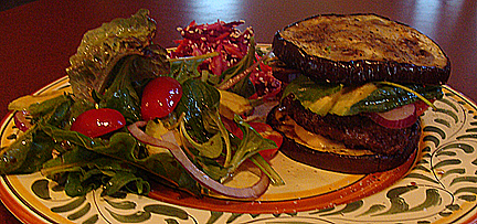 """A burger of grass-fed beef served up on a grilled eggplant """"bun,"""" and sides of weedy salad greens from the expansive Jackass on the Run Gardens and Rootin' Tootin' Summer Salad."""