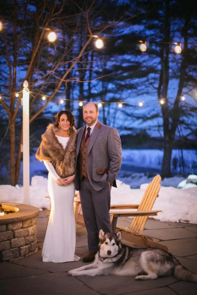 Dog lays with couple on wedding day by fire pit