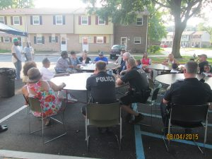 Havre de Grace police officers and residents of Somerset Manor talk about community safety during National Night Out 2015, an event held around the country to build positive relationships between citizens and law enforcement.