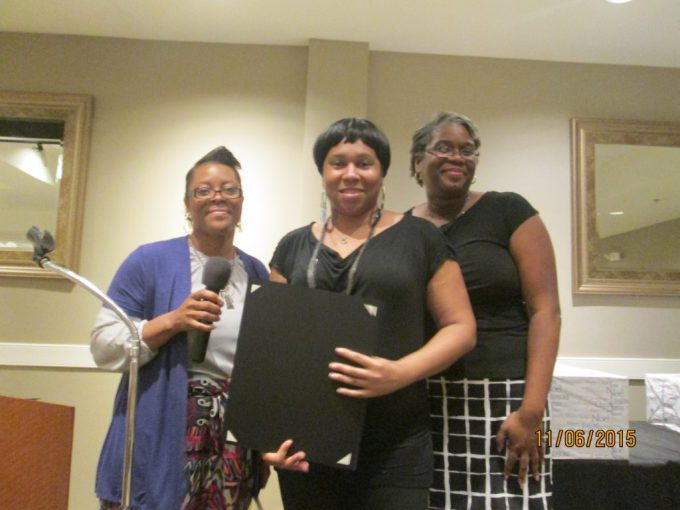 Ann Chealey (left), the Family Self-Sufficiency Program Coordinator, and Nicki Biggs (right), Executive Director of The SUCCESS Project, present Sheree Sumler with a certificate of recognition.