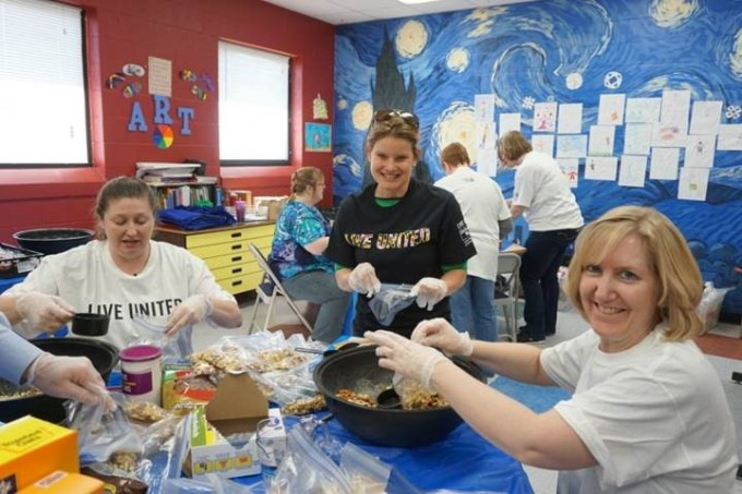 Pictured from left to right are Kattie Badders and Amber Shrodes from the Harford County Dept. of Community Services working with Joan Ingold, Dept. of Information and Communication Technology, to make trail mix included in 150 bagged lunches for the boys and girls.