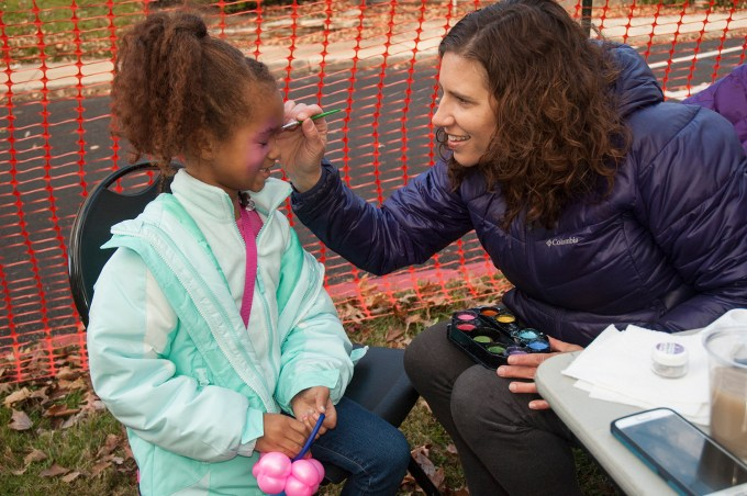 Audra Hurd, Heather Hurd's aunt, paints the face of Alani McPherson in the children's area at the 8th Annual Heather L. Hurd 5K Run and Kids Trick or Treat Walk on October 29 at Harford Community College. (Photo by Lauren Ciambruschini/Harford Community College)