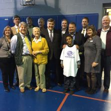 Congressman Ruppersberger stands for a photo with Boys & Girls Club Staff and Board of Directors. Kai Pettigen, 10 years old, wanted to join the photo as well.