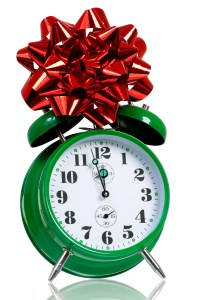 Alarm clock with red gift bow. Time for the holiday's concept with clock and present isolated on white background.