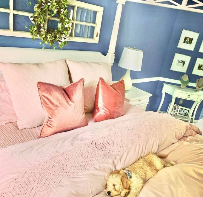 clean bed with pink comforter and pillows