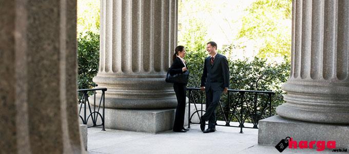 Ilustrasi: dua orang pengacara berkomunikasi di luar pengadilan