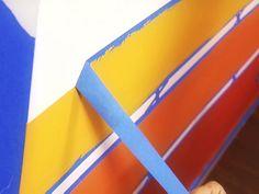 Gunakan selotip untuk mengecat tembok dengan pola garis.