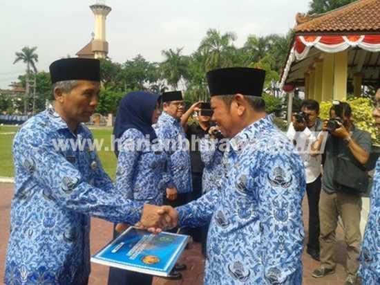 Bupati Saiful Ilah menyerahkan secara simbolis kartu tanda anggota KORPRI kepada Kepala BPPT kab Sidoarjo, Ahmad Zaini. [alikusyanto/bhirawa]