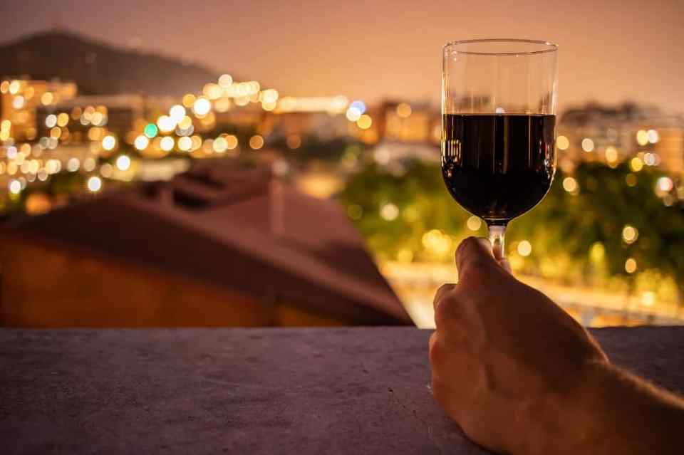 glass of red wine held in front of city lights