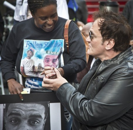 Kimberly Griffin, left, holds hands with film director Quentin Tarantino after she recalled memories of her son Kimoni Davis, during a public reading of the names of people who have died at the hands of police nationwide, Thursday, Oct. 22, 2015, at Times Square, in New York. The protest marked the start of three days of protests and marches speaking out against violence at the hands of law enforcement. (AP Photo/Bebeto Matthews)
