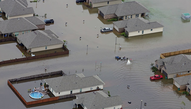 In this aerial photo a boat motors between flooded homes after heavy rains inundating the region Saturday, Aug. 13, 2016, in Hammond, La. Louisiana Gov. John Bel Edwards says more than 1,000 people in south Louisiana have been rescued from homes, vehicles and even clinging to trees as a slow-moving storm hammers the state with flooding. (AP Photo/Max Becherer)