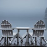 Empty wooden table and chairs facing foggy lake