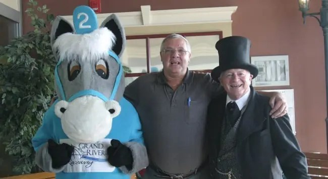 Grand River Raceway mascot Grandy with longtime guest Ray Rowarth and Greeter Tom Williams. For the past decade, Tom has greeted guests at the front door every race night | Iron Horse Photo