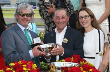 Claus Andersen | Two-time Hambletonian champion Blair Burgess (left) was on hand to present the winning trainer trophy to fellow Canadian Rick Zeron (with wife Joyce Zeron).