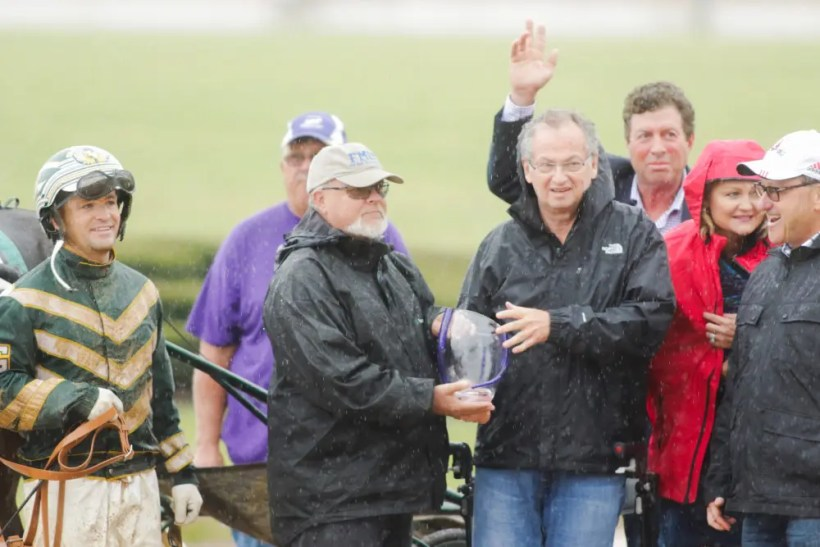 Dave Landry | Al Libfeld (front right with trophy) with some of his important friends and team members (from left): driver Yannick Gingras, yearling-picking expert Perry Soderberg (also with trophy), Jimmy Glass (arm raised), Christina Takter and Sam Goldband after Libfeld's beloved Ariana G won a heat of the 2017 Kentucky Filly Futurity.