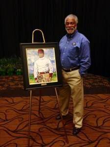 Harold Michael Harvey posing alongside the portrait of William Clarence Matthews during Matthews induction into the College Baseball Hall of Fame in the 2014 class. Harvey a former baseball player at Tuskegee represented Matthews at the induction ceremony.