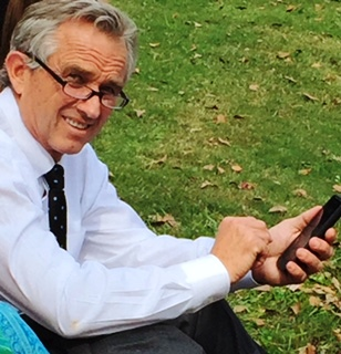 Robert F. Kennedy, Jr. sitting on a grassy knoll checking his messages while waiting to address the truth, transparency and freedom rally at Grant Park in Atlanta, Georgia October 24, 2015 Photo Credits: (c) Harold Michael Harvey