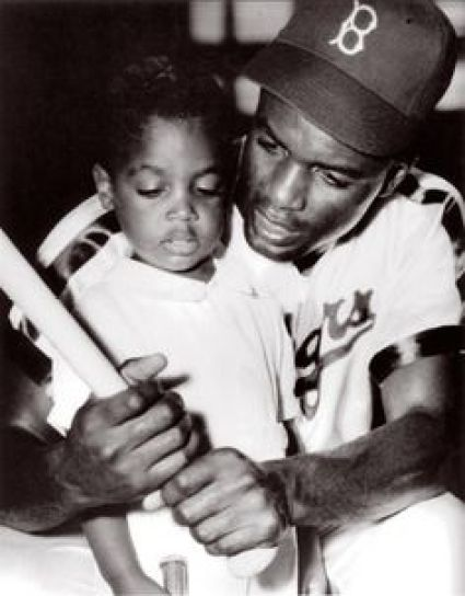 Jackie Robinson with his son showing him how he used a baseball bat to break down barrier. Photo Credit:Pinterest.com