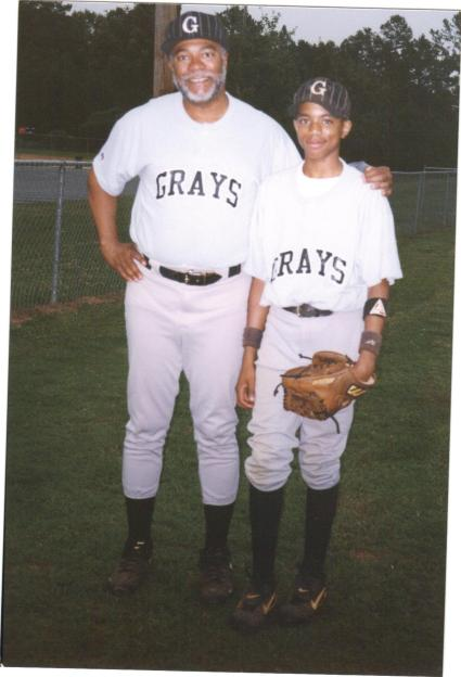 Father and son posing for a photo in 1999 the year their team won the Sandy Koufax District Tournament. Photo Credits (c) 1999 C. M. Harvey