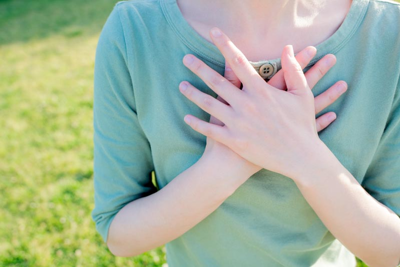 woman's hands over chest representing self-acceptance