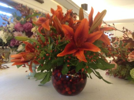 A bowl of cranberries holds flowers and rose hips in place