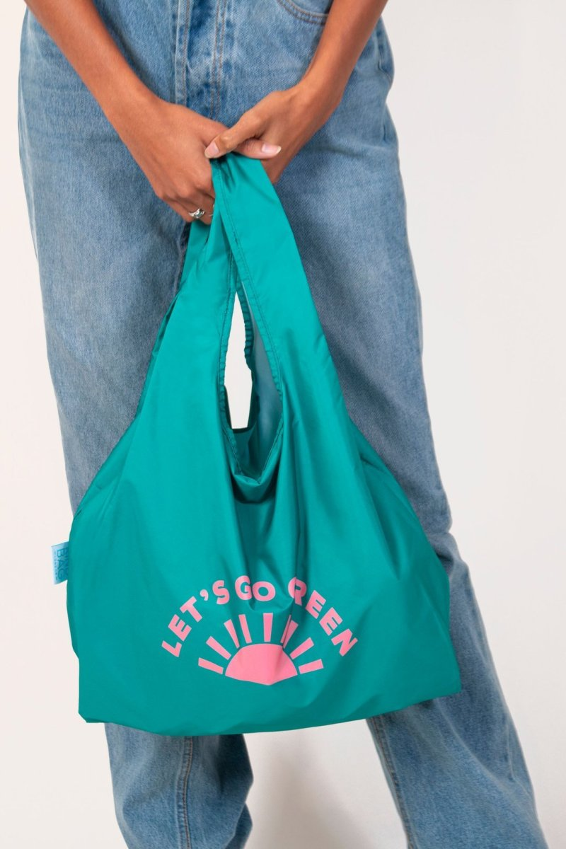 person holding lets go green kind bag
