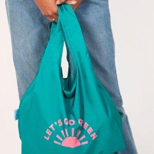 person holding lets go green kind bag
