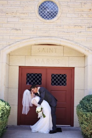 Bride and groom embracing in front of church