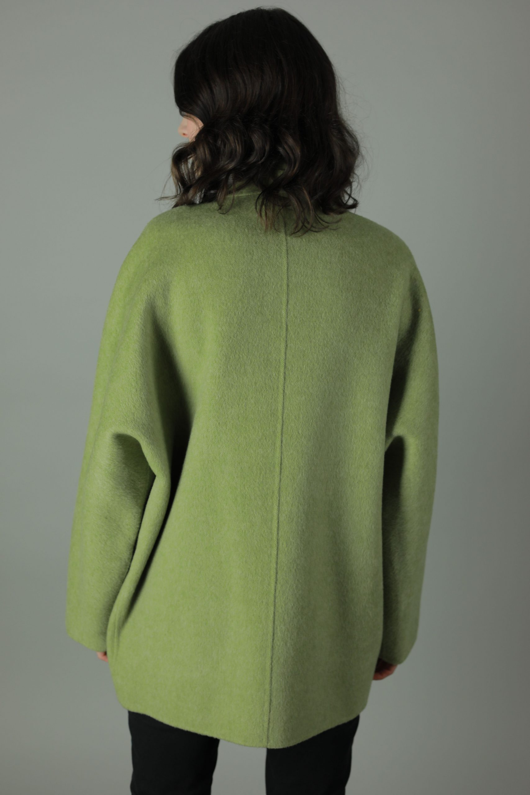Luxury in The Chloe Cashmere Coat. Thigh length for all round wear, this coat features 100% soft Cashmere, loose fitting style, two front patch pockets and beautiful white soft cashmere interior for inside out look. Back view.