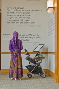 A person wearing a hijab stands next to a baby carriage in front of a wall with quotes.