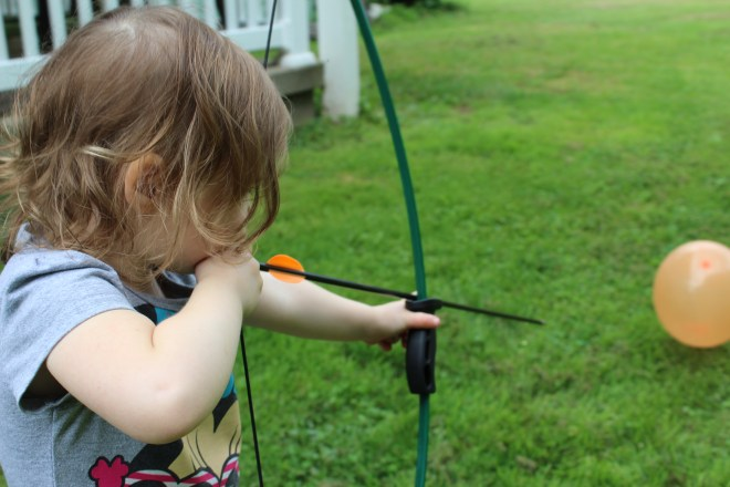 My Daughter learning the finer points of archery while shooting at balloons in our backyard.