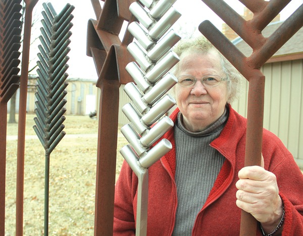 Marjorie Shoemaker is the director of the Mennonite Heritage and Agricultural Museum in Goessel, Here, she stands by a wheat sculpture on the museum grounds. It was made by Arlie J. Regier. Wendy Nugent / The Edge