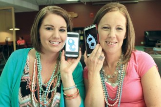 Amy Curiel, left, and Amy Church hold their cell phones, which they use a great deal in their Premier Jewelry businesses, with photos of earrings on them up to their ears, as virtual earrings, of sorts. Wendy Nugent/The Edge