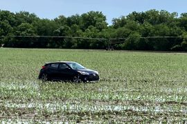Photo shows car in a field from flood waters.